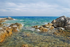 Sunny coastal landscape with rocks, agitated sea and cloudy sky. For tourism Royalty Free Stock Images