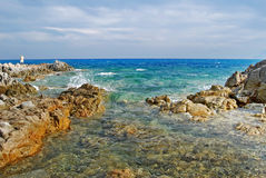 Sunny coastal landscape with rocks, agitated sea and cloudy sky. For tourism Stock Image