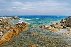 Sunny coastal landscape with rocks, agitated sea and cloudy sky. For tourism stock image