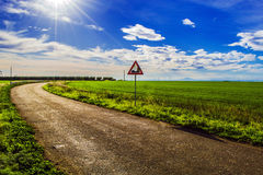 Sunny country road. Blue sky with clouds Stock Image