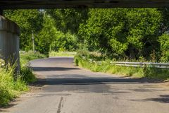 Sunny Cracked Rural Road. Old cracked, damaged asphalt road in countryside at sunny day Stock Image