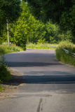 Sunny Cracked Rural Road. Old cracked, damaged asphalt road in countryside at sunny day Royalty Free Stock Photography