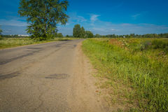 Sunny Cracked Rural Road. Old cracked, damaged asphalt road in countryside at sunny day Royalty Free Stock Images
