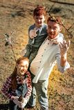 Sunny cute red-haired smiling family looking for trees royalty free stock photo