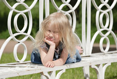 Sunny day. Little blonde girl laying on the bench in park stock photos