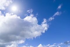 Sunny day. Sun shining brightly in a cloudy sky Royalty Free Stock Image