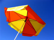 Sunny Day. Red-yellow sun umbrella on blue sky stock photo