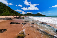 Sunny day on the beach. A beautiful brazilian beach in a bright sunny day. Green mountains, blue sky and white clouds on the background Stock Photos
