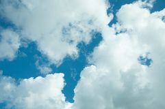 Fluffy white clouds and blue summer skies. A sunny day with a blue sky and some fluffy cumulus clouds royalty free stock photography