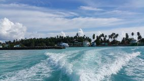 Waves on the foreground with Kudahuvadhoo island with speedboats and  palmtrees at the background. Sunny day with blue sky and white clouds. Wave can be seen at Royalty Free Stock Photos