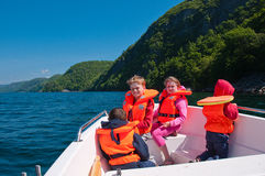 Sunny day in a boat. Kids in lifejackets floating in a boat in sunny summer day royalty free stock photo
