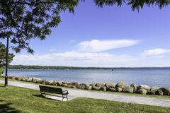 Bench along sidewalk on the shoreline of Canandaigua Lake. Sunny day and calm water on the lake. Rocks on the shoreline. Boats on the lake stock image