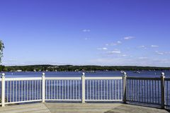 Canandaigua Lake and horizon view from the gazebo i. Sunny day and calm water on the lake. Wood deck and railing of the gazebo in the park stock photography
