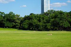 Sunny day in city park in Budapest with two people on green grass. And skyscraper on the background Stock Photo