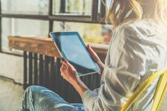 Sunny day. Close-up of tablet computer in hands of young woman sitting in room on chair.Hipster girl working online Stock Photography
