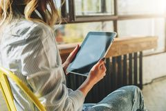 Sunny day. Close-up of tablet computer in hands of young woman sitting in room on chair.Hipster girl working online Royalty Free Stock Photos