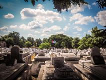 View of the a cementery in Havana with cuban flag. A sunny day at the Colon cemetery in Vedado, havana with a cuban flag at the center Stock Photo