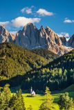 Sunny day in Dolomites, Tirol. The symbol of the valley Val di Funes - church of Santa Maddalena. Rocky peaks and forested mountains surrounded by green stock photos