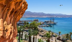 Sunny day in Eilat - famous resort city in Israel. View on central beach, promenade and marina with pleasure boats, yacht and motorboat for rent Royalty Free Stock Photography