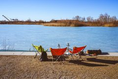 Sunny day on the frozen lake with camping chairs royalty free stock image