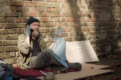 Sunny day, homeless old man charging phone from solar battery. Old tramp living in the streets and modern gadgets stock images