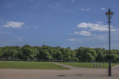 Sunny day in Hyde Park and a lamp post. This image shows some meadows in the Hyde Park and a big stretch of a blue sky. There`s a lamp post visible in the Royalty Free Stock Image
