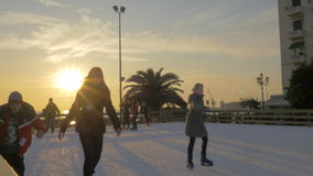 In sunny day on ice rink at Aristotelous square skating children and young people stock video
