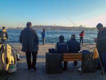Sunny day in Karakoy Beach Fishermen Istanbul. Sunny day in istanul Karakoy Some People Sitting Some People Fishing in Bosphorus Royalty Free Stock Images