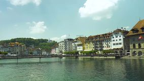 Sunny day in Luzern Switzerland with people walking on the bridge and enjoying beautiful panoramic view of the old town buildings. And Chapel bridge Kapellbr stock video footage