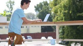 Sunny Day, mananseende och maskinskrivning på bärbara datorn i balkong arkivfilmer