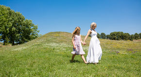 Sunny day, mother and little girl walking in the field. Happy mom and daughter spending time together outdoors Stock Image