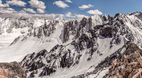 Sunny day in the mountains of Kyrgyzstan in the mountaineering camp. Bright sunny day, snow-white glaciers and steep cliffs. Wide panorama of mountain scenery Stock Image