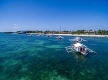 Sunny Day na ilha de Malapascua no mar do Visayan, uma da ilha de Cebu Água do mar e barcos Praia da recompensa com arquitetura l Fotografia de Stock