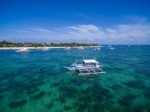 Sunny Day na ilha de Malapascua no mar do Visayan, uma da ilha de Cebu Água do mar e barcos Praia da recompensa com arquitetura l Foto de Stock Royalty Free