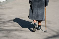 On a sunny day a old woman walking down the street with walking. Stick. The woman`s shadow is visible on the sidewalk. View from the back Royalty Free Stock Photo