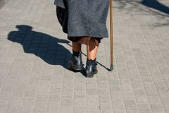 On a sunny day a old woman walking down the street with walking. Stick. The woman`s shadow is visible on the sidewalk. View from the back Stock Photo