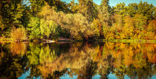 Sunny day in outdoor park with autumn trees reflection. Sunny day in outdoor park with lake and colorful autumn trees reflection under blue sky. Amazing bright stock photos