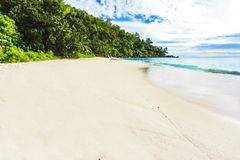 Sunny day on paradise beach anse georgette,praslin seychelles 4. Sunny day on paradise beach with big granite rocks, turquoise water, white sand and palm trees Royalty Free Stock Image