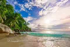 Sunny day on paradise beach anse georgette,praslin seychelles 45. Sunny day on paradise beach with big granite rocks, turquoise water, white sand and palm trees stock photo