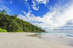 Sunny day on paradise beach anse georgette,praslin seychelles 5. Sunny day on paradise beach with big granite rocks, turquoise water, white sand and palm trees Royalty Free Stock Photography