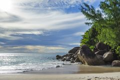 Sunny day on paradise beach anse georgette,praslin seychelles 1. Sunny day on paradise beach with big granite rocks, turquoise water, white sand and palm trees Royalty Free Stock Images