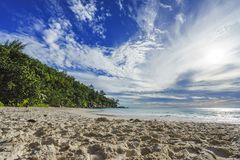 Sunny day on paradise beach anse georgette,praslin seychelles 2. Sunny day on paradise beach with big granite rocks, turquoise water, white sand and palm trees Stock Photography