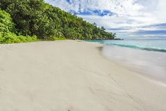 Sunny day on paradise beach anse georgette,praslin seychelles 4. Sunny day on paradise beach with big granite rocks, turquoise water, white sand and palm trees Stock Photo