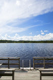 Sunny day at the pier. The ladders goes to the deep water. Some dramatic clouds are in the sky. Image taken in Finland during summer day stock photo