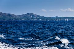 View of the white waves left by the motorboat. Sunny day, sea view to the coast; view of the white waves left by the motorboat; on the shore there are large royalty free stock photography
