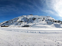 Sunny day at the Ski Resort of Warth, Austria. Different Ski pistes at a ski resort and a very nice cloudshape Royalty Free Stock Photo