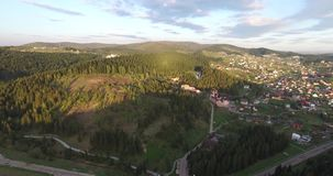 Sunny day in small town at the foot a hill. Small town is situated on low hill, green hilly terrain, hillsides in the green pine trees and firs, low houses with stock footage