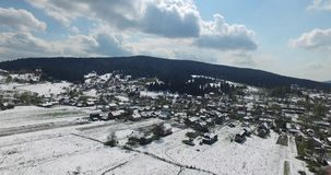 Sunny day on a small village on the hillside. Green forest with spruce fir tree in mountains, roofs of houses and roads in the snow, smoke from chimney, aerial stock footage