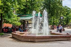 Apatin, Vojvodina, Serbia. A sunny day in spring with terraces with people passing by a fountain in the center of Apatin stock images