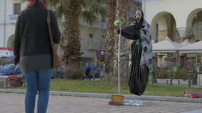 In sunny day a street performer in costume of death shows a trick how to fly in the air stock video